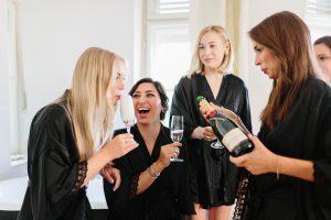 Die Braut lacht vor Freude beim einschenken des Champagner, Hochzeit Alte Gärtnerei - Alexandra Kasper