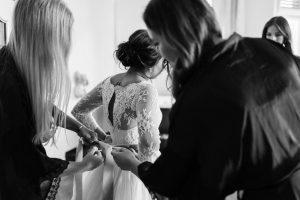 Die Braut und die Freundinnen von hinten beim Kleid anziehen helfen, Hochzeit Alte Gärtnerei - Alexandra Kasper