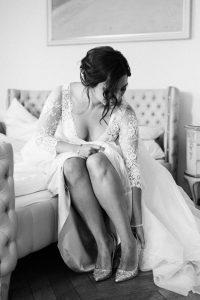 Die Braut während dem Schuhe anziehen auf dem Bett sitzend, Hochzeit Alte Gärtnerei - Alexandra Kasper