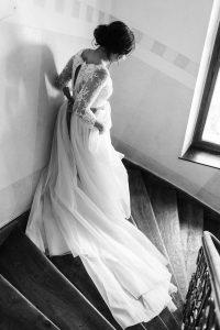 Die Braut von hinten auf dem Weg die Treppe hinunter im Hotel Mariandl, Hochzeit Alte Gärtnerei - Alexandra Kasper