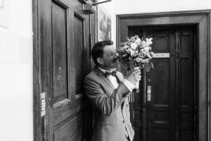 Der Bräutigam versteckt sich hinter dem Brautstrauß kurz bevor er die Braut sieht, Hochzeit Alte Gärtnerei - Alexandra Kasper