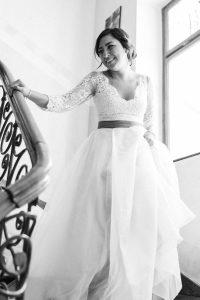 Die Braut auf dem Weg die Treppe hinunter im Hotel Mariandl, Hochzeit Alte Gärtnerei - Alexandra Kasper