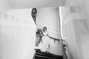 Das Brautpaar auf dem Weg die Treppe hinunter im Hotel Mariandl, Hochzeit Alte Gärtnerei - Alexandra Kasper