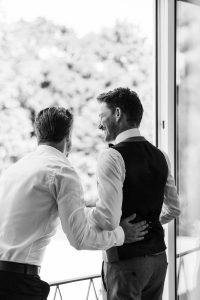 Portrait vom Bräutigam mit einem guten Freund beim Getting Ready am Fenster, Hochzeit Alte Gärtnerei - Alexandra Kasper