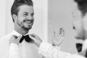 Aufnahme vom Bräutigam beim Getting Ready während dem anziehen der Fliege, Hochzeit Alte Gärtnerei - Alexandra Kasper