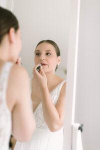 Die Braut beim auftragen des Lippenstift vor dem Spiegel, Hochzeitsfotograf Bodensee - Alexandra Kasper
