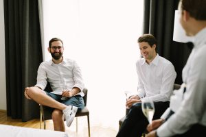 Der Bräutigam im Gespräch mit Freunden im Hotelzimmer, Hochzeitsfotograf Bodensee - Alexandra Kasper