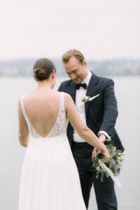 Der Bräutigam schaut sich das Kleid der Braut genauer an, Hochzeitsfotograf Bodensee - Alexandra Kasper