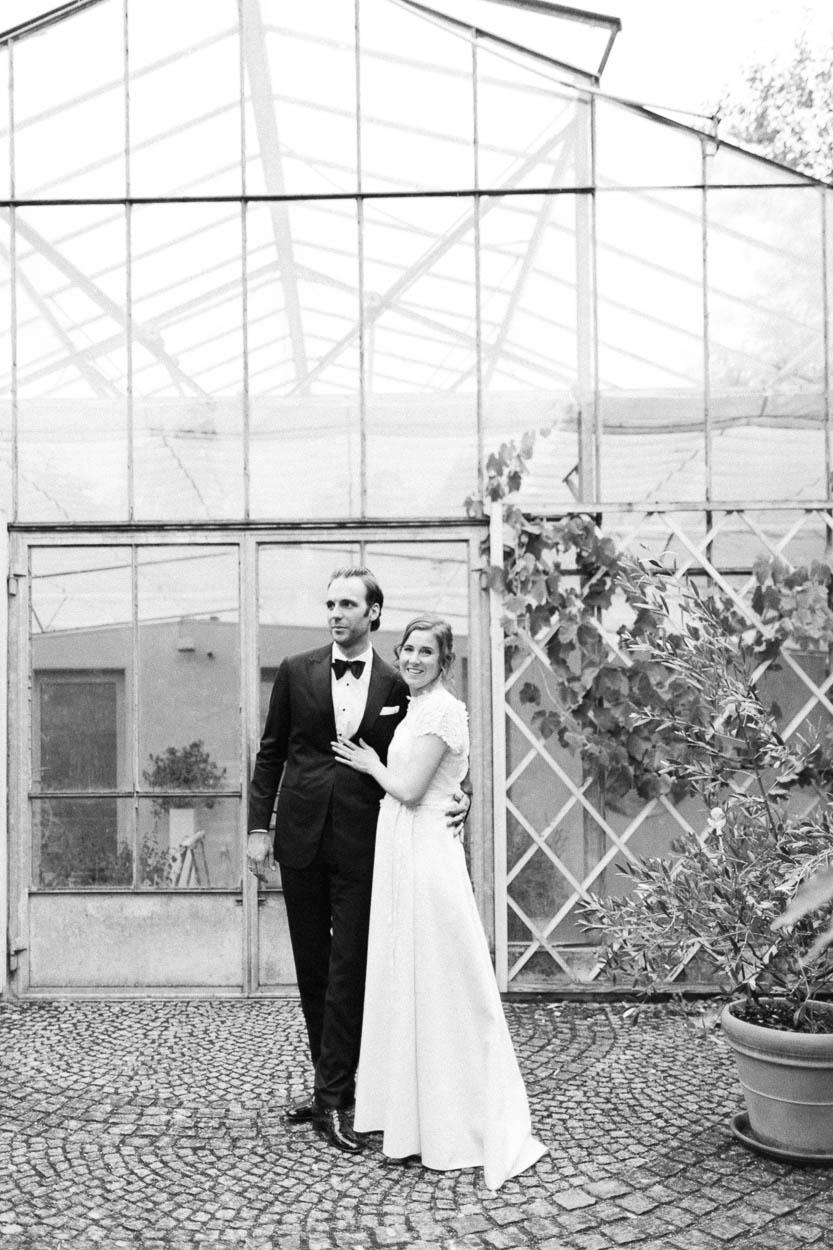 Das Hochzeitspaar vor einem Gewächshaus in der Alte Gärtnerei, Alexandra Kasper - Alte Gärtnerei