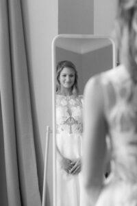 Portrait der Braut während sie sich selbst im Spiegel anschaut, Hochzeit Gut Sonnenhausen - Alexandra Kasper