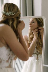 Die Braut beim anziehen der Ohrringe vor dem Spiegel, Hochzeit Gut Sonnenhausen - Alexandra Kasper