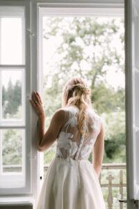 Die Braut lehnt im Fensterrahmen und blickt nach draussen, Hochzeit Gut Sonnenhausen - Alexandra Kasper