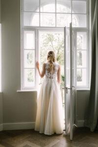 Die Braut fotografiert von hinten wie sie im Fenster steht, Hochzeit Gut Sonnenhausen - Alexandra Kasper