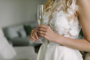 Nahaufnahme der Braut mit einem Glas Champagner in der Hand auf Gut Sonnenhausen, Hochzeit Gut Sonnenhausen - Alexandra Kasper
