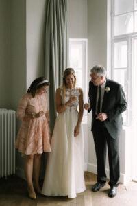 Momentaufnahme der Braut, Trauzeugin und Vater beim anstossen mit Champagner, Hochzeit Gut Sonnenhausen - Alexandra Kasper