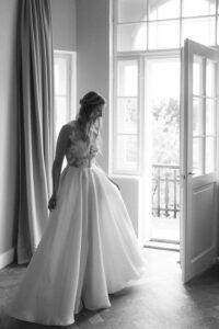 Die Braut betrachtet sich nach dem Getting Ready im Spiegel im Kleid von Kaviar Gauche, Hochzeit Gut Sonnenhausen - Alexandra Kasper