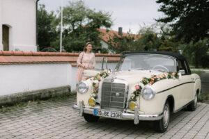 Das Brautauto vor der Kirche im Portrait, Hochzeit Gut Sonnenhausen - Alexandra Kasper