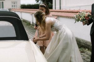 Das Brautauto wird von der Braut abgesperrt und steht vor der Kirche, Hochzeit Gut Sonnenhausen - Alexandra Kasper