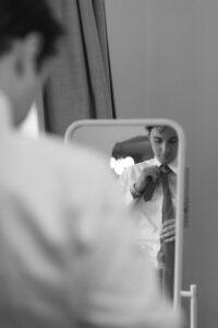 Portrait vom Bräutigam beim anlegen der Krawatte vor dem Spiegel, Hochzeit Gut Sonnenhausen - Alexandra Kasper