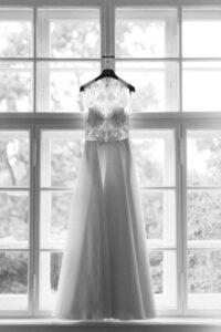 Das Brautkleid von Kaviar Gauche hängt im Fenster, Hochzeit Gut Sonnenhausen - Alexandra Kasper