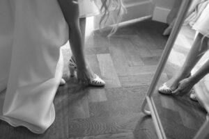 Nahaufnahme der Braut beim Schuhe anziehen auf Gut Sonnenhausen, Hochzeit Gut Sonnenhausen - Alexandra Kasper