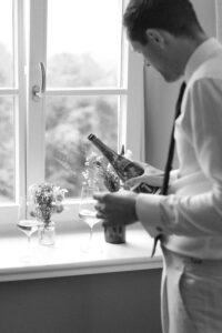 Der Trauzeuge vom Bräutigam schenkt Wein ein am Fenster im Sengerschloss am Tegernsee, Hochzeit am Tegernsee - Fährhütte 14, Alexandra Kasper