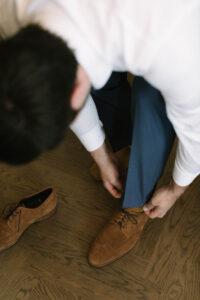 Der Bräutigam beim Schuhe anziehen im Sengerschloss am Tegernsee, Hochzeit am Tegernsee - Fährhütte 14, Alexandra Kasper