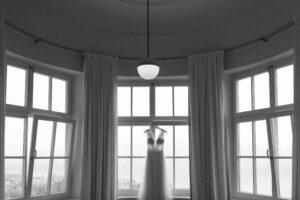 Das Brautkleid hängend im Fenster aufgenommen im Sengerschloss am Tegernsee, Alexandra Kasper - Hochzeitsfotograf Tegernsee