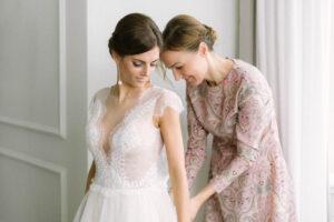 Die Braut zieht mit Hilfe der Trauzeugin das Brautkleid an, Alexandra Kasper - Hochzeitsfotograf Tegernsee