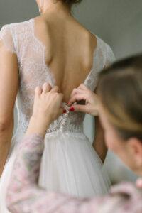 Detailaufnahme der Trauzeugin beim schließen des Brautkleids, Alexandra Kasper - Hochzeitsfotograf Tegernsee
