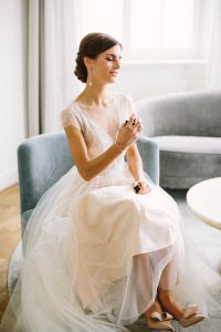 Die Braut beim aufsprühen des Parfüm im sitzen, Alexandra Kasper - Hochzeitsfotograf Tegernsee