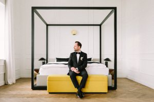 Portrait vom Bräutigam auf dem Bett sitzend, Alexandra Kasper - Hochzeitsfotograf Tegernsee