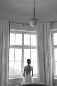 Die Braut blickt auf den Tegernsee vom Sengerschloss aus, Alexandra Kasper - Hochzeitsfotograf Tegernsee
