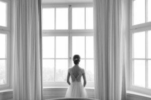 Die Braut steht am Fester von hinten aufgenommen, Alexandra Kasper - Hochzeitsfotograf Tegernsee
